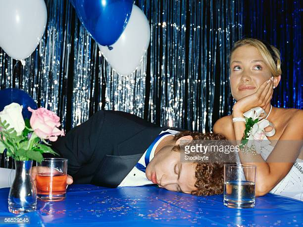 teenage boy lying unconscious on a table with a teenage girl sitting beside him