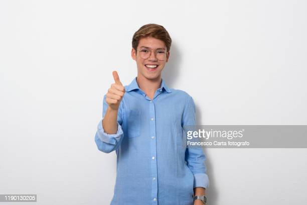 teenage boy making ok hand sign - 親指 ストックフォトと画像