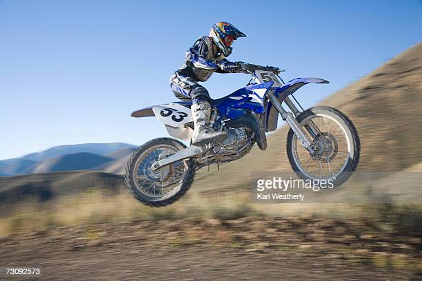 teenage boy (13-15) motorbiking down dirt road - scrambling stock photos and pictures