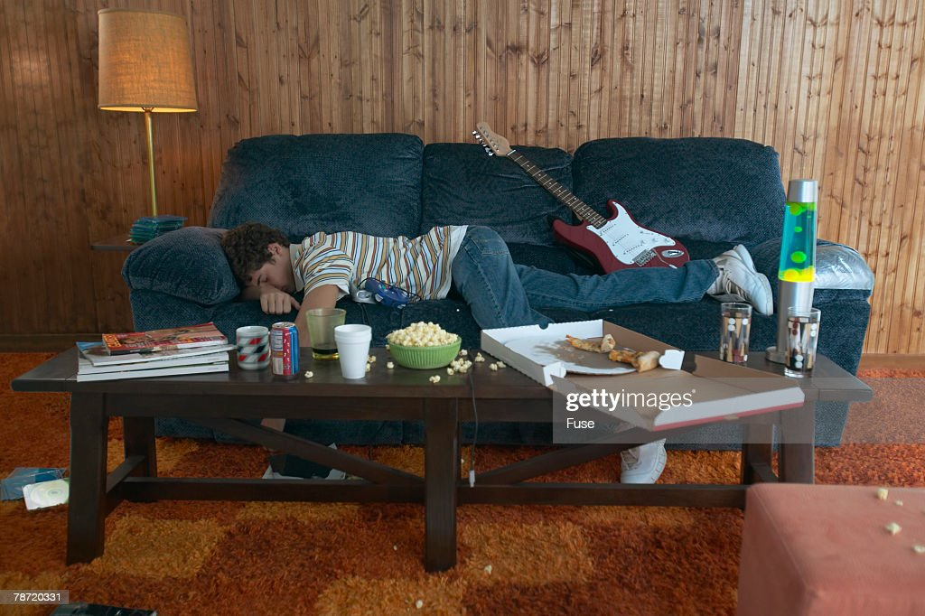 Teenage Boy Napping in Messy Living Room : Stock Photo