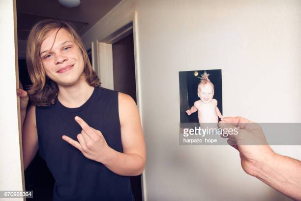 Teenage boy next to a photo of himself as a toddler.