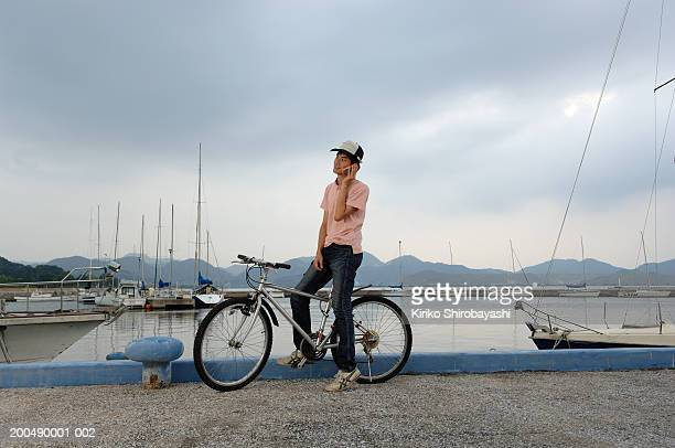 teenage boy (17-19) on bicycle at waterfront using mobile phone, dusk - yonago stock photos and pictures