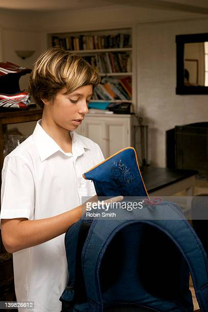 Teenage boy packing school bag at home