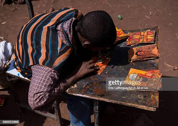 Teenage boy painting some orthodox icons amhara region lalibela Ethiopia on February 23 2016 in Lalibela Ethiopia