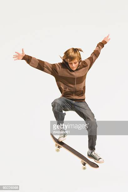 Teenage boy (14-15) performing jump on skateboard, arms out