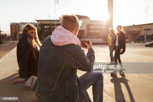 teenage boy photographing friends skateboarding at park - fotohandy stock-fotos und bilder