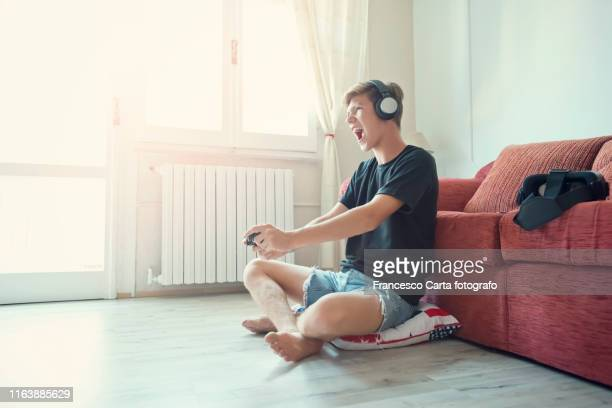 teenage boy  playing at video game - leisure games ストックフォトと画像