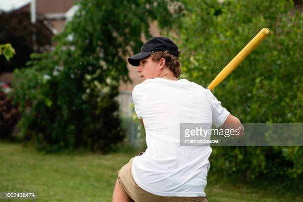 """teenage boy playing baseball in suburb park. - """"martine doucet"""" or martinedoucet stock pictures, royalty-free photos & images"""