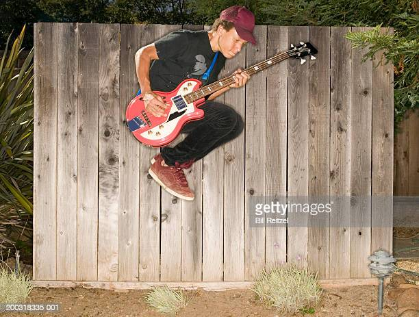 Teenage boy (13-15) playing bass guitar, jumping in midair, side view