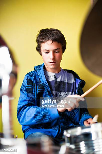 Teenage boy playing drums with a concentration expression