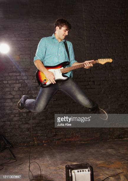 teenage boy playing electric guitar and jumping above amplifier - one teenage boy only stock pictures, royalty-free photos & images