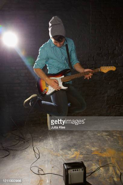 teenage boy playing electric guitar, jumping above amplifier - one teenage boy only stock pictures, royalty-free photos & images