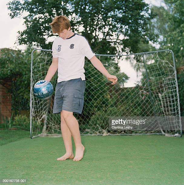 Teenage boy (15-17) playing football in garden