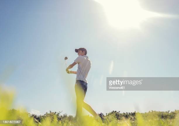 teenage boy playing golf against clear sky during sunny day - golf stock pictures, royalty-free photos & images
