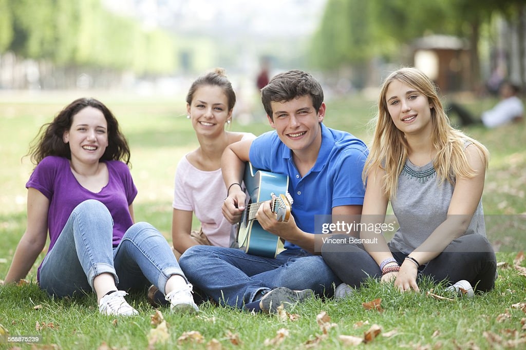 A teenage boy playing guitar in a park : Stock Photo