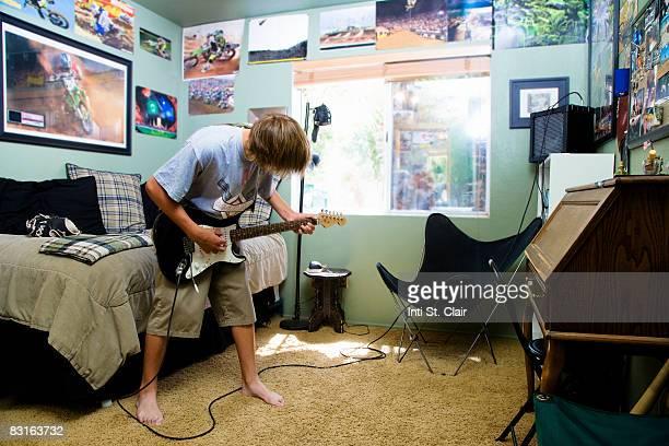 teenage boy playing guitar in bedroom - ベースギター ストックフォトと画像