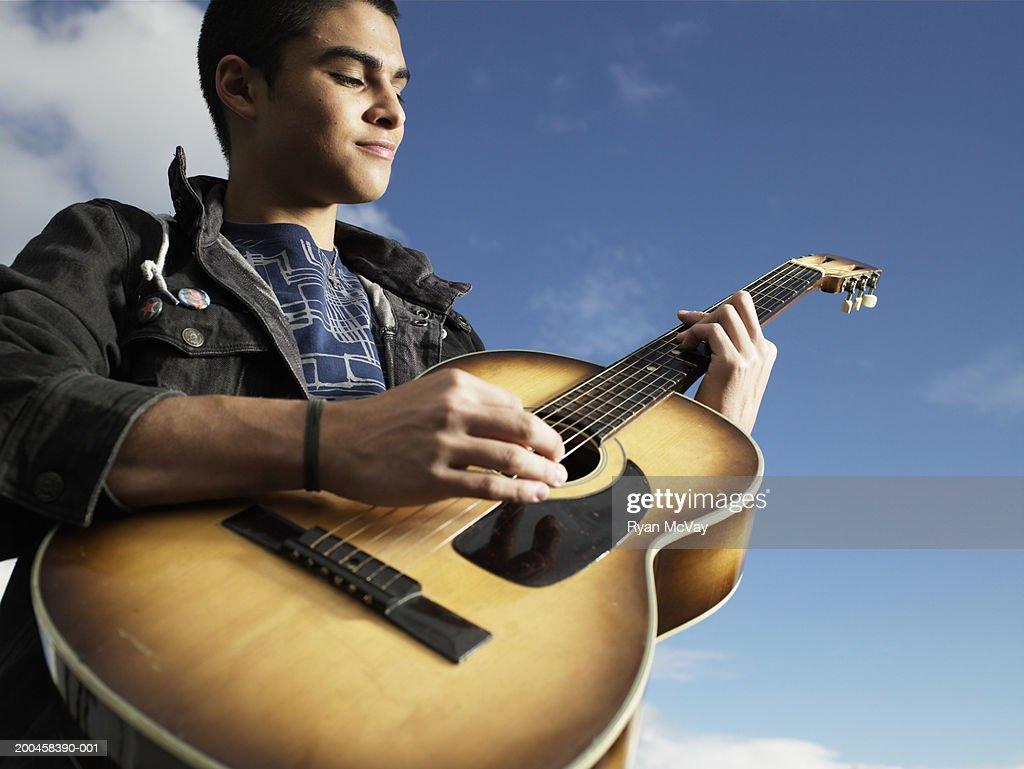 Teenage boy (15-17) playing guitar, low angle view : Stock Photo