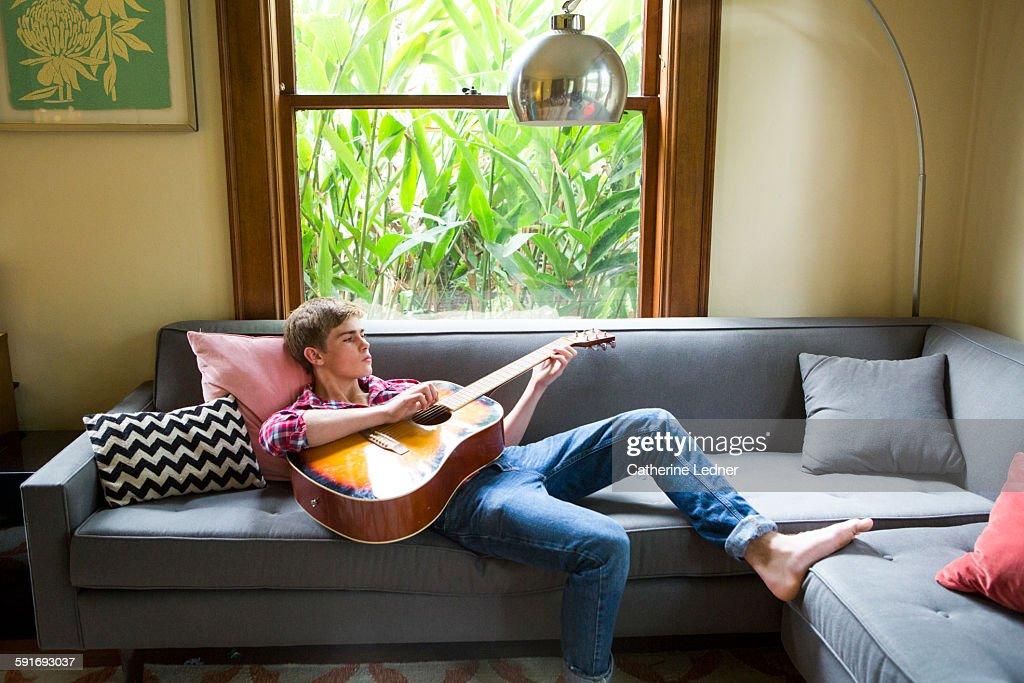 Teenage Boy Playing Guitar On Living Room Sofa : Stock Photo