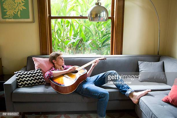 teenage boy playing guitar on living room sofa - teen boy barefoot stock photos and pictures