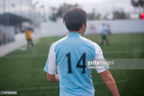 teenage boy playing indoor soccer wearing light blue jersey number 14 - youth sports competition stock pictures, royalty-free photos & images