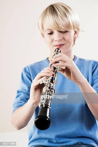 teenage boy playing oboe - oboe stock-fotos und bilder