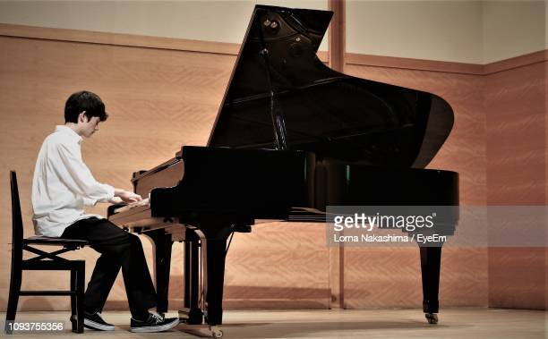 teenage boy playing piano - grand piano stock pictures, royalty-free photos & images