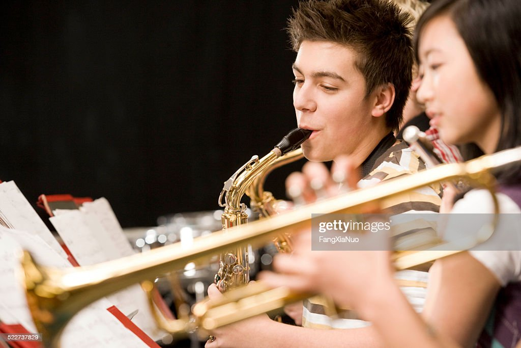 Teenage boy playing saxophone in high-school band : Stock Photo