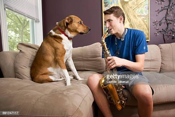 Teenage boy playing saxophone next to dog