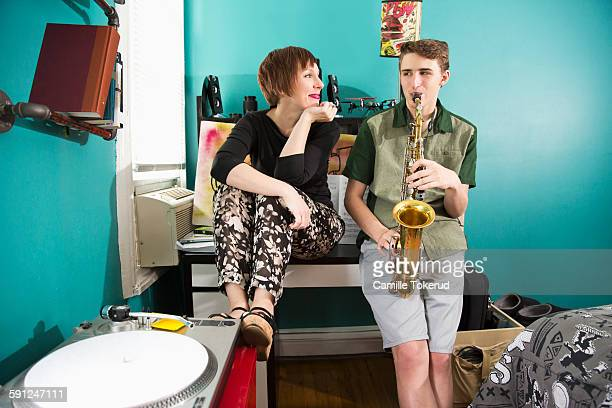 Teenage boy playing saxophone next to mother