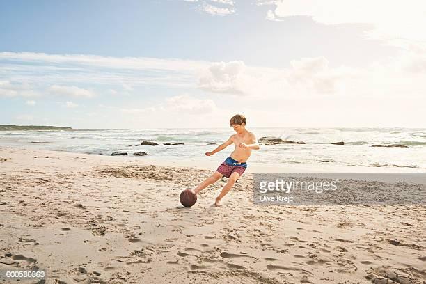 Teenage boy playing soccer on beach