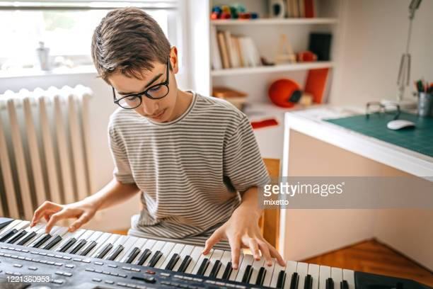 teenage boy playing the keyboard - keyboard player stock pictures, royalty-free photos & images