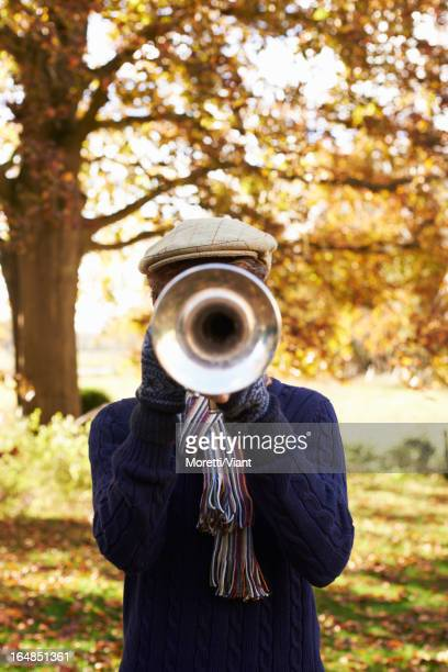 Teenage boy playing trumpet outdoors
