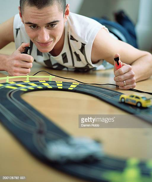 Teenage boy (15-17) playing with electric slot car, ground view