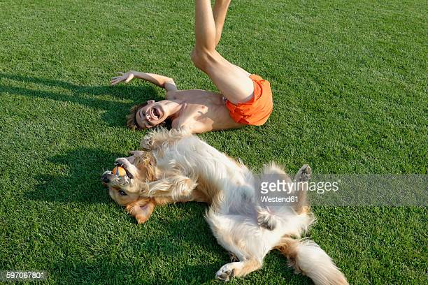 Teenage boy playing with Golden Retriever on lawn