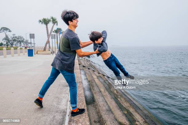 teenage boy playing with little brother next to large body of water - flowering plant stock pictures, royalty-free photos & images