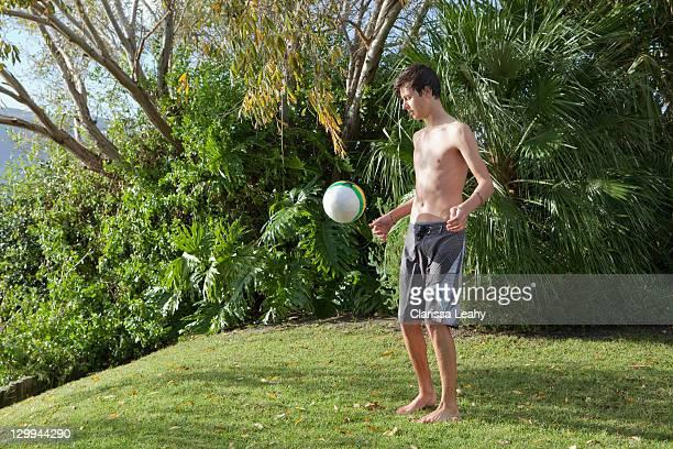 jeunes garçons jouant avec un ballon de football - un seul jeune garçon photos et images de collection