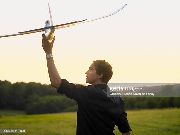 Teenage boy (16-18) playing with toy aeroplane in field, rear view