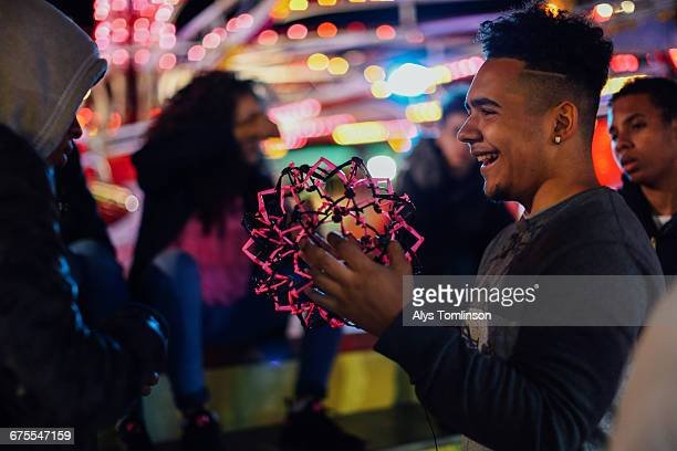 teenage boy playing with toy at fairground