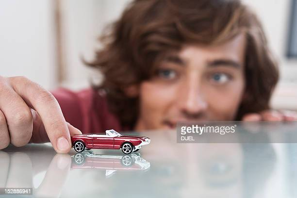 Teenage boy playing with toy car