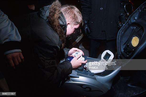 A teenage boy plays a playstation installed on a scooter Luton UK 2004