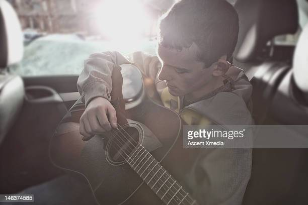 Teenage boy plays guitar in rear seat of car