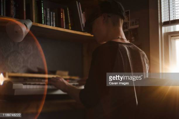 teenage boy plays keyboard in bedroom during sunset - keyboard player stock pictures, royalty-free photos & images