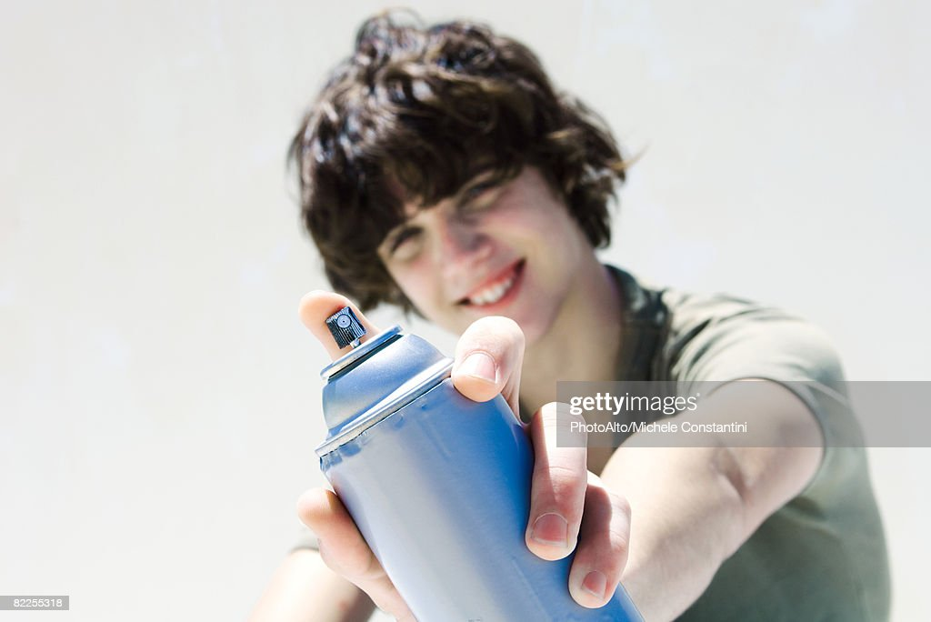 Teenage boy pointing can of spray paint at camera, focus on the foreground : Stock Photo