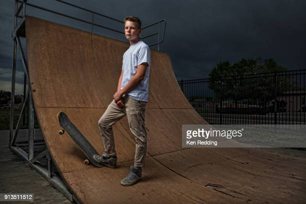 Teenage boy posing with skateboard on half pipe