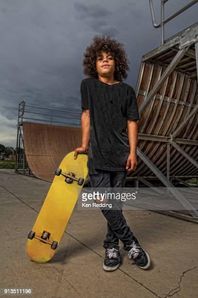 Teenage boy posing with skateboard