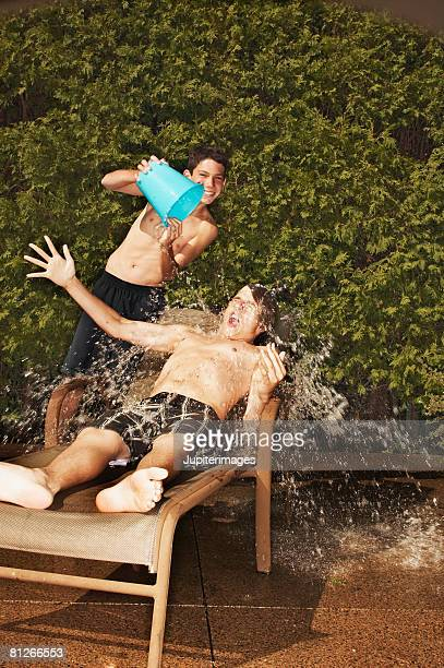 Teenage boy pouring water on friend