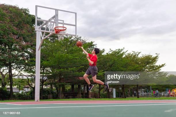 tonårspojke övar basket layup på domstol nära bostadsområde - poängräkning bildbanksfoton och bilder