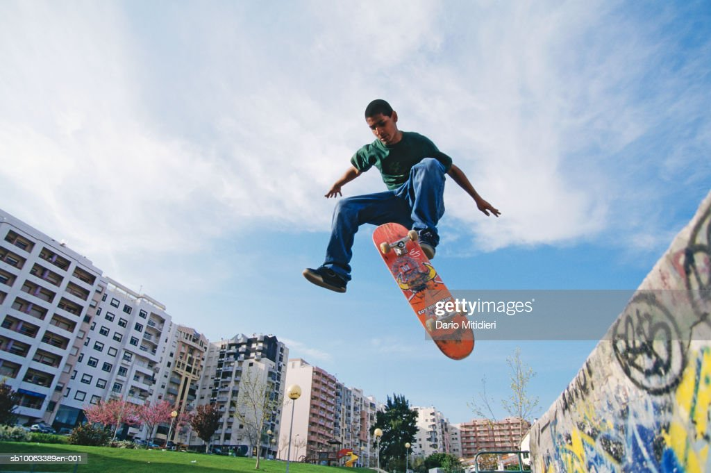 Teenage boy (16-17) practicing skateboard trick, low angle view : News Photo