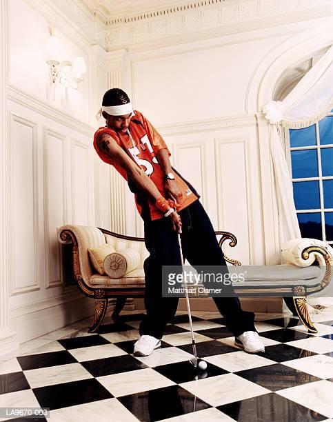 Teenage boy (16-18) practising golf indoors