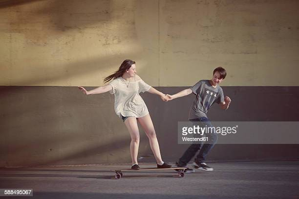 Teenage boy pulling his girlfriend standing on a longboard